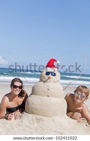 Perfectly build christmas snowman made out of sand and pretty couple enjoying beach. With sunglasses and copy space in the blue sky. - stock photo