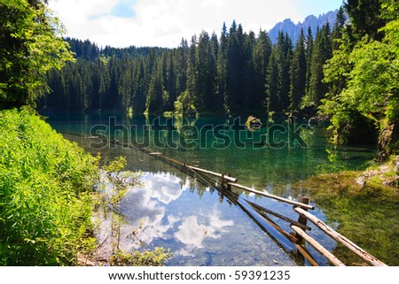 Perfectly clear emerald lake in Dolomites - stock photo