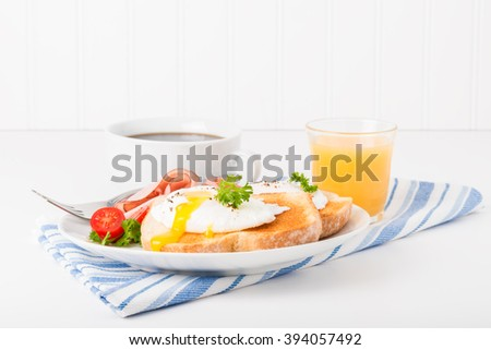 Perfectly poached egg on toast with ham. - stock photo