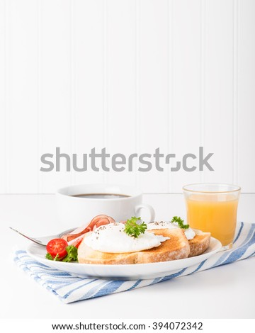 Perfectly poached eggs on toast with ham. - stock photo