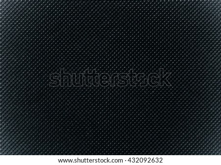 perforated black textile pattern texture background or backdrop with soft vignette