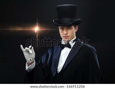 performance, circus, show concept - magician in top hat with magic wand showing trick - stock photo