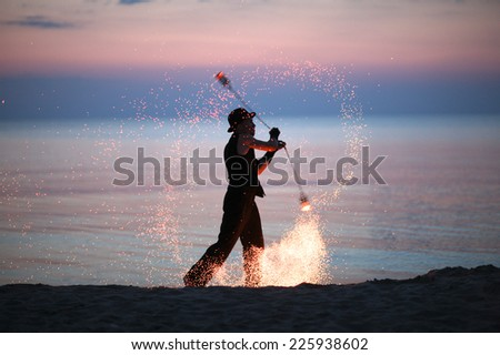 Performer spinning fire poi outdoors - stock photo