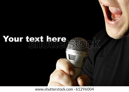 Performer with microphone close-up over black background - stock photo