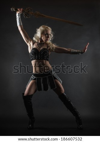 Performer woman wearing sexy costume and holding a sword, grey smoky background
