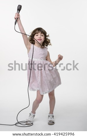 Performing little artist professionally poses and looks in the camera. Young caucasian singer rises her hand with the microphone and smiles. Atmosphere of joy. - stock photo