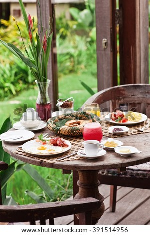 Perfrect healthy breakfast on patio in summer day. Fried eggs, cappuccino, fruits and muesli. Yummy and delicious