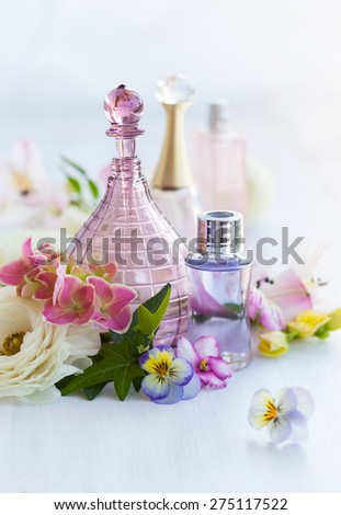 perfume and aromatic oils bottles surrounded by fresh flower - stock photo