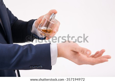 Perfume aroma. Person holding perfume with one hand and spraying it on his wrist. - stock photo