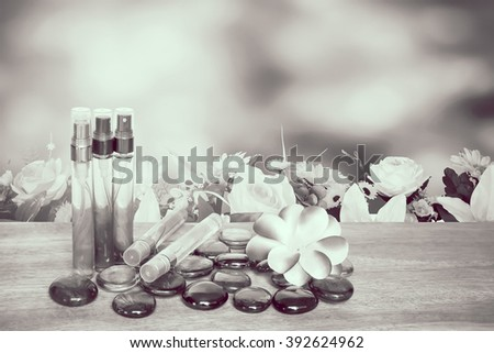 perfume bottle and flower with florist with blur bush background - stock photo