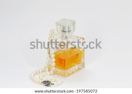 Perfume bottle and  pearls necklace. - stock photo