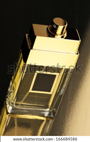 Perfume bottle on gold background with reflection. - stock photo