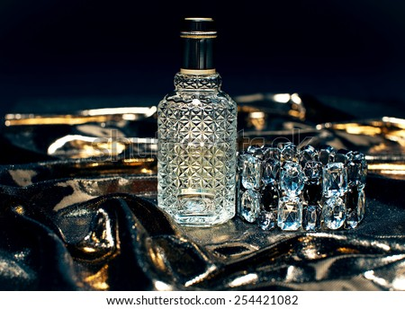 Perfume bottle on golden background - stock photo