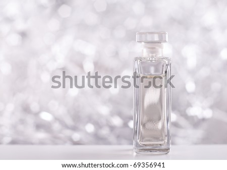 Perfume bottle on sparkling background - stock photo