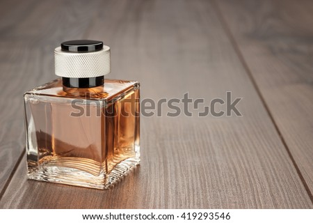 perfume bottle on the brown wooden table background - stock photo