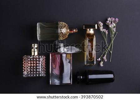 perfume bottles surrounded by flower on black background. - stock photo