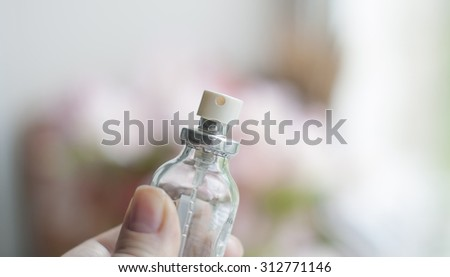 Perfume bottles with spray on blurry daylight  background