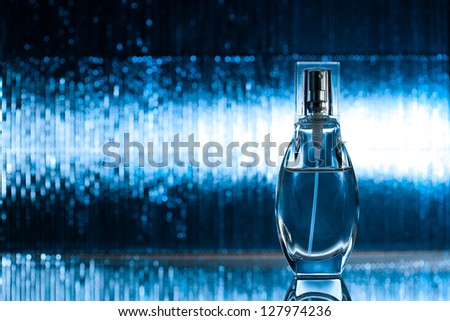 Perfume on abstract blue background - stock photo