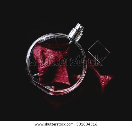 Perfume with a petals of rose on black - stock photo