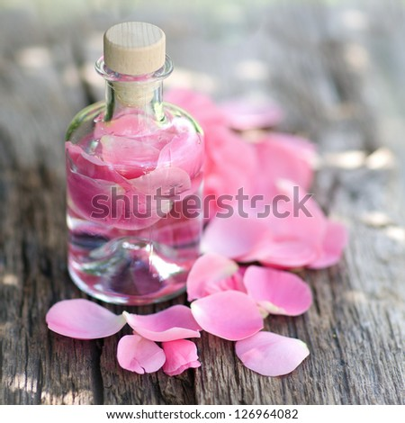 Perfume with rose leaves - stock photo
