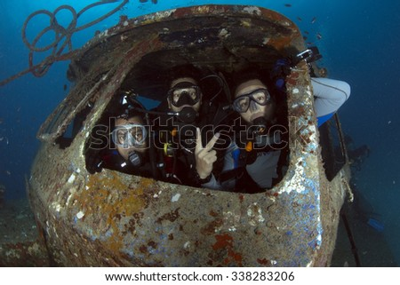 PERHENTIAN ISLAND, Malaysia, June 17, 2014:  Divers enjoying their diving in the police ship wreck. They are 3 unit police ship wreck to attrack tourist in Perhentian Island, Malaysia. - stock photo