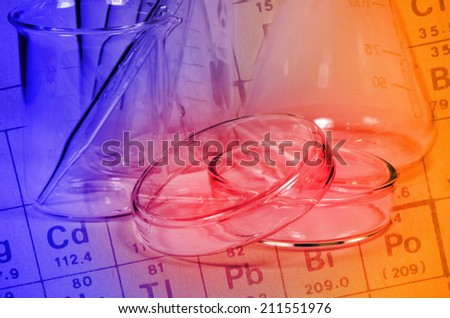 Periodic table of Elements and laboratory glassware in Laboratory Experiment. - stock photo
