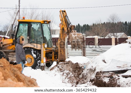 PERM, RUSSIA, DECEMBER 15.2015: excavator working on a construction site, dig a trench for fence