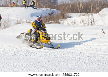 Perm, Russia - February 23, 2015. Championship on Cross Country Snowmobiles. man on yellow  Snowmobile  enters  sharp turn day