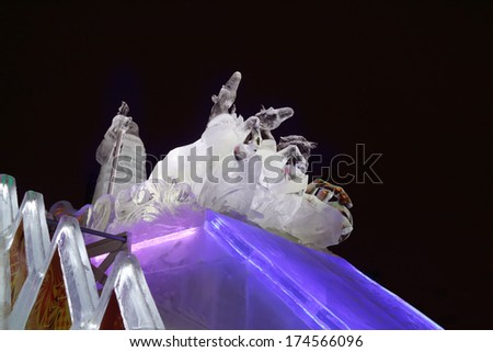 PERM, RUSSIA - JAN 11, 2014: Horse triple and Santa sculpture in Ice town at evening. Construction of Ice town of Perm was spent 590 thousand dollars. - stock photo