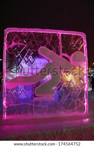 PERM, RUSSIA - JAN 11, 2014: Illuminated pink Skater character sculpture in Ice town at evening, created in honor of Winter Olympic Games 2014 will be in Sochi, Russia.