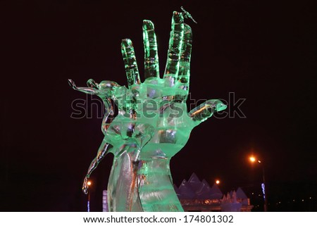 PERM, RUSSIA - JAN 11, 2014: Sculpture Hand and dancing woman in Ice town at evening. Construction of Ice town of Perm was spent 590 thousand dollars. - stock photo