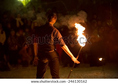 Perm, Russia - January 17, 2015. man in  black suit standing with  fiery stick his back