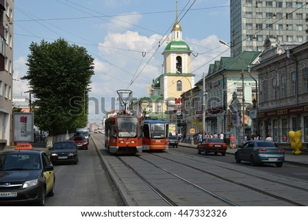 Perm, Russia - 20 June 2016. Tram in city surrounds. Tramway and motor-car traffic at Lenina Street, one of the central thoroughfares of the city. Roadbed overhaul preparations with partly cut asphalt