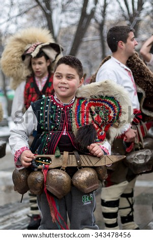 "PERNIK, BULGARIA - JANUARY 26, 2014: A boy in a folklore costume marching and smiling during a traditional Bulgarian festival for banishing evil spirits called ""Surva""."