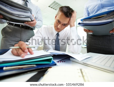 Perplexed accountant doing financial reports being surrounded by business partners with huge piles of documents - stock photo