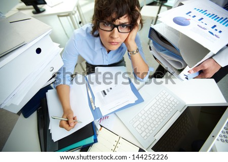 Perplexed accountant doing financial reports being surrounded by huge piles of documents - stock photo