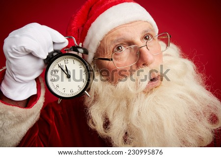Perplexed Santa holding clock showing five minutes to xmas by his ear - stock photo