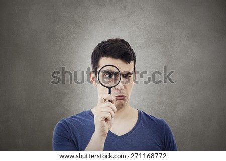 Perplexed Young man student holding magnifying glass isolated over grey background. - stock photo