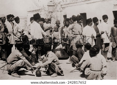 Persian Cossack Brigade, Russian styled elite Iranian military unit, shown at mealtime, ca. 1910. From its officer ranks, General Reza Khan emerged to overthrow Ahmad Shah Qajar in 1925. - stock photo