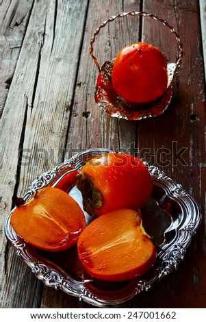 Persimmon and cut persimmon on rustic wooden background. - stock photo
