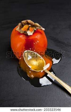 persimmon with honey on black - stock photo