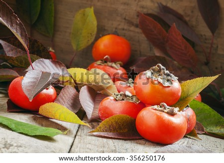 Persimmons with leaves on the old wooden table, selective focus - stock photo