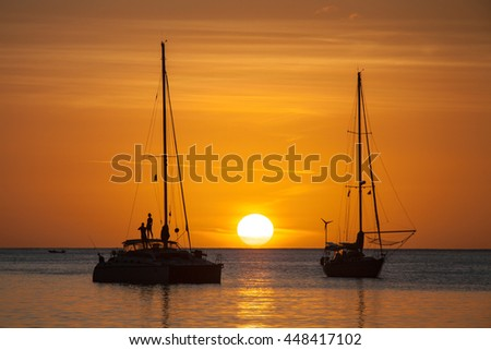 Person and sailboat in silhouette at Caribbean ocean, vivid bright sky. Large white sun on horizon at sunset. Man and woman stand on a boat. Colorful orange sky with cloud streaks in Saint Lucia. - stock photo