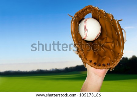 person catching baseball in leather baseball glove outdoors - stock photo
