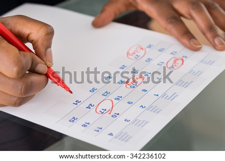 Person Circling Important Date On Calendar With Red Marking - stock photo