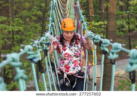 Person climbing on a rope at the adventure park - stock photo