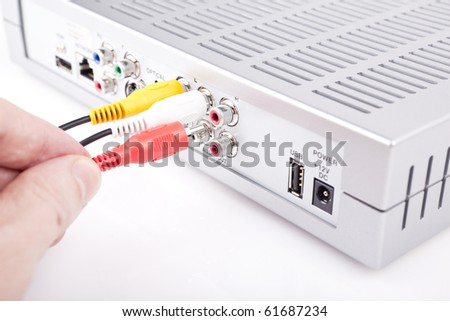 Person connecting AV cables at the back of device - stock photo