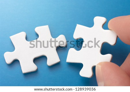 Person connecting two puzzle pieces.Concept image of building.