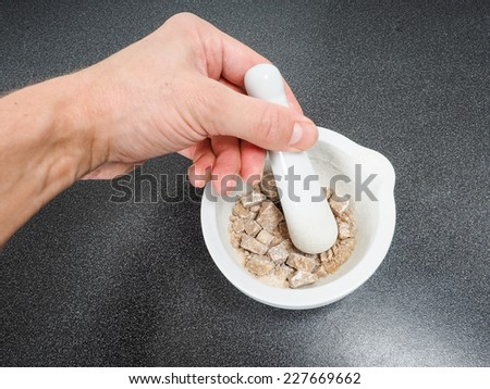 Person crushing brown sugar cubes in a white marble mortar on black table - stock photo