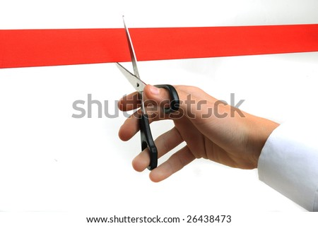 Person cutting red ribbon with scissors - stock photo